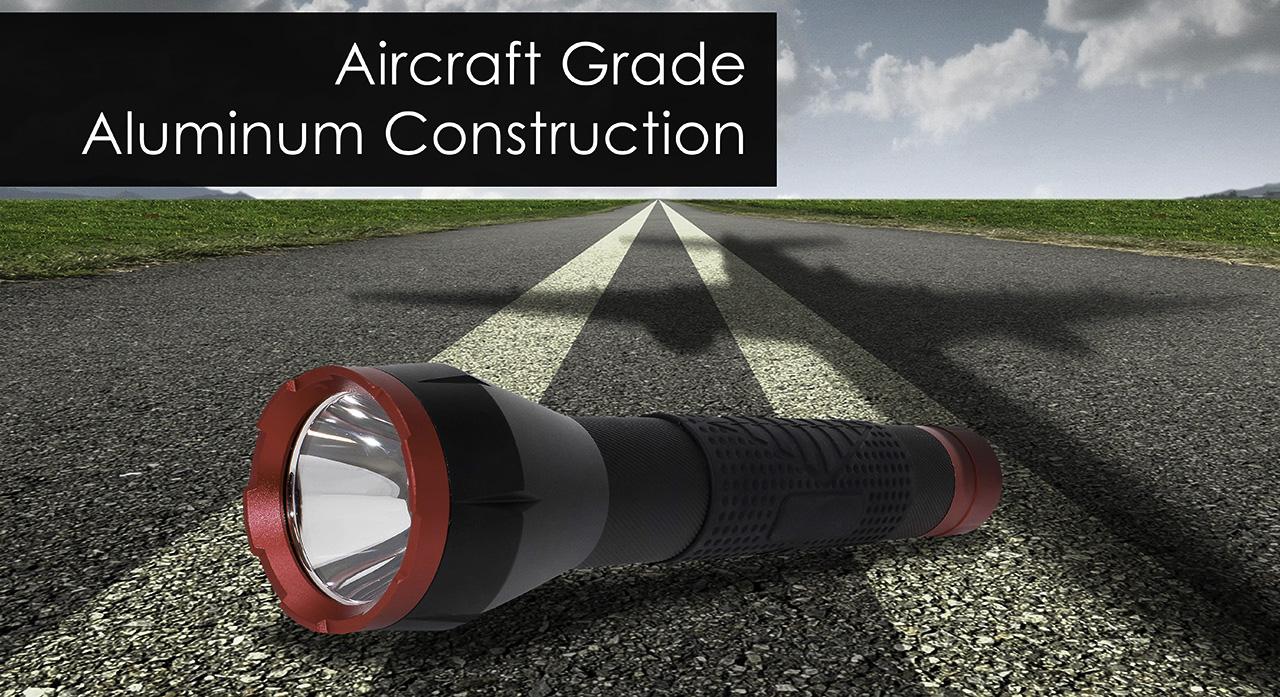 The BB-1K - 1000 Lumen LED Flashlight on the tarmac beneath the shadow of a jet.