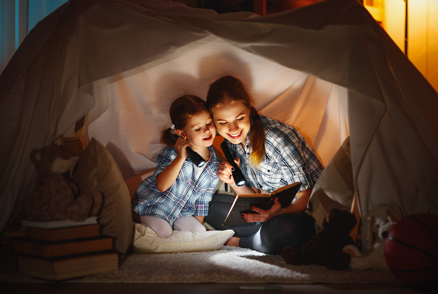 A woman and young girl use their Smartech Everbright 250 Lumen Ultra Bright CREE XPG LED Tactical Flashlights to illuminate the pages of their bedtime storybook.